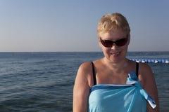 Frau von mittlerem Alter in einem pareo und in der Sonnenbrille Lizenzfreies Stockbild
