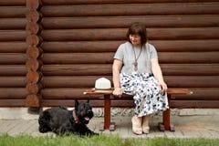 Frau von mittlerem Alter in einer Landschaft, die auf einer Holzbank sitzt und einen schwarzen Schnauzer nahe einem Blockhaus bet Stockbild