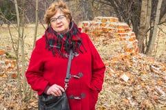 Frau von mittlerem Alter mit Gläsern und einer roten Jacke stockfotos