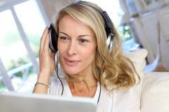 Frau von mittlerem Alter mit Kopfhörern und Tablette Stockfotografie