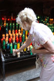 Frau von mittlerem Alter setzt eine Kerze in heilige Stätte ein Lizenzfreies Stockfoto