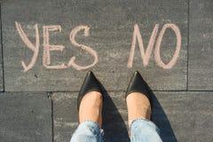 Frau vor der Wahl ja oder nein Ansicht von oben, weibliche Füße mit des Textes keinem ja geschrieben auf grauen Bürgersteig Stockbild
