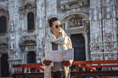 Frau vor Duomo in Mailand mit der Karte, die Abstand untersucht Lizenzfreie Stockbilder