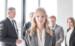 Frau vor Geschäftsteam Stockfoto