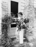 Frau vor ihrem Haus, das Blumen in ihren Armen erfasst (alle dargestellten Personen sind nicht längeres lebendes und kein Zustand Stockfotos