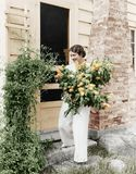 Frau vor ihrem Haus, das Blumen in ihren Armen erfasst (alle dargestellten Personen sind nicht längeres lebendes und kein Zustand Lizenzfreies Stockbild