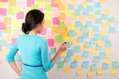 Frau vor Wand mit vielen Aufklebern Stockfotografie