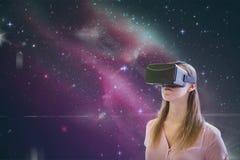 Frau in VR-Kopfhörer, der gegen rosa Galaxiehintergrund schaut Lizenzfreie Stockfotos