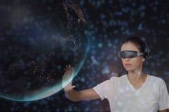 Frau in VR-Kopfhörer, der Planeten 3D gegen schwarzen Hintergrund mit Grünem und Purpur berührt, erweitert sich Stockfotografie