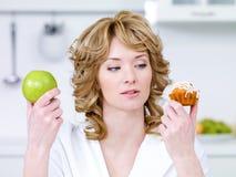 Frau wählen zwischen Kuchen und Apfel Stockfoto