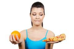 Frau wählen zwischen Pizza und Orange Lizenzfreie Stockfotos