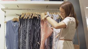 Frau wählt ein Kleid im Speicher stock footage