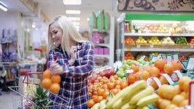 Frau wählt Frucht in einem Supermarkt stock footage