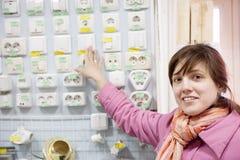 Frau wählt Schalter im elektrischen Speicher lizenzfreie stockbilder