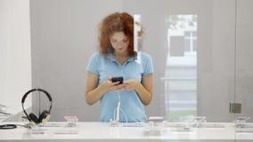 Frau wählt Smartphone in einem Speicher stock video