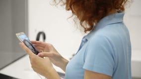 Frau wählt Smartphone in einem Speicher stock footage
