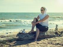 Frau während einer Pause zwischen Sitzungen mit Eignung durch das Meer Stockfotos