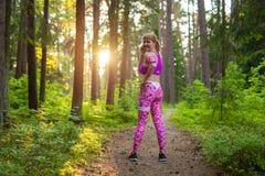Frau während ihres Laufs durch Holz Stockbild