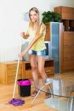 Frau wäscht den Fußboden mit Mopp Stockbild