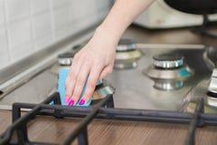 Frau wäscht einen Ofen Stockbild