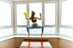 Frau wäscht Fenster in einer Yogahaltung Stockfotos