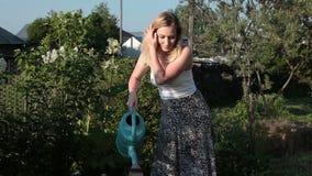 Frau in wässernblumen des Gartens stock video
