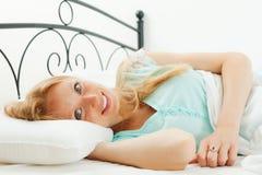 Frau wacht in ihrem Bett auf Lizenzfreie Stockfotos
