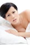 Frau wacht im Bett auf Stockfotografie