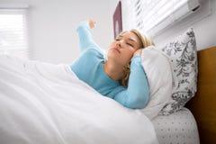 Frau weckt vom langen Schlaf im Bett, das morgens an einem sonnigen Tag gähnt und ausdehnt Lizenzfreie Stockfotos