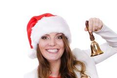 Frau in Weihnachtsmann-Hut, der eine Glocke schellt Stockfotos