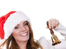 Frau in Weihnachtsmann-Hut, der eine Glocke schellt Lizenzfreies Stockfoto