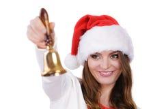 Frau in Weihnachtsmann-Hut, der eine Glocke schellt Stockfotografie