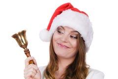 Frau in Weihnachtsmann-Hut, der eine Glocke schellt Stockbild