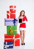 Frau in Weihnachtsmann-Stoff, der leeren Bildschirm zeigt Stockfotos