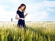 Frau am Weizenfeld am sonnigen Tag Stockfotografie