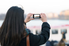 Frau, welche Ansicht die im Freien unter Verwendung des Handys vertritt Stockfotos