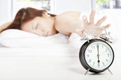 Frau, welche die Alarmuhr abstellt lizenzfreies stockfoto