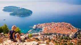 Frau, welche die alte Stadt Dubrovniks betrachtet Lizenzfreies Stockfoto