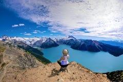 Frau, welche die Ansicht von alpinem See umgeben mit Schnee mit einer Kappe bedeckten Bergen genießt Lizenzfreies Stockbild