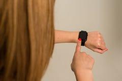 Frau, welche die Apple-Uhr berührt Lizenzfreie Stockfotografie