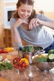 Frau, welche die Beiträge zu ihrer Mahlzeit würzt lizenzfreies stockfoto