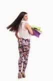 Frau, welche die Einkaufstaschen zurück schauen hält Lizenzfreies Stockfoto