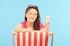 Frau, welche die Eiscreme gesetzt auf Sonnenruhesessel isst Stockbild