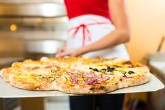 Frau, welche die fertige Pizza vom Ofen drückt Stockfoto