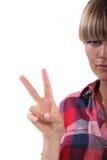 Frau, welche die Friedensgeste bildet Lizenzfreie Stockfotografie