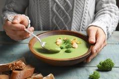Frau, welche die Frischgemüse Detoxsuppe bei Tisch gemacht vom Brokkoli mit Croutons isst lizenzfreie stockfotografie