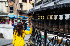 Frau, welche die Gebets-Räder am Affe-Tempel Swayambhunath in Kathmandu, Nepal dreht Lizenzfreie Stockbilder