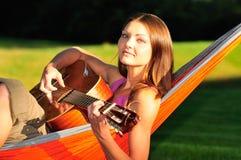 Frau, welche die Gitarre spielt Lizenzfreie Stockfotografie