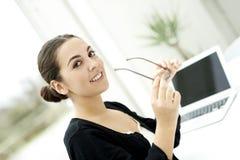 Frau, welche die Gläser lächeln an der Kamera hält Lizenzfreie Stockbilder