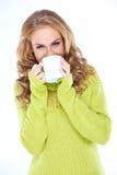 Frau, welche die grüne Strickjacke trinkt vom Becher trägt Lizenzfreies Stockfoto